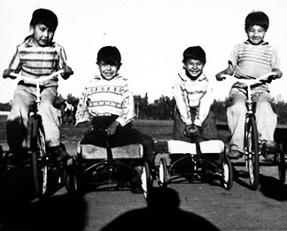 Charley Chisaakey, Rene Natammak, Eric Kolay and S. Didzena ride their bikes and wagons at Assumption Residential School in June 1959.