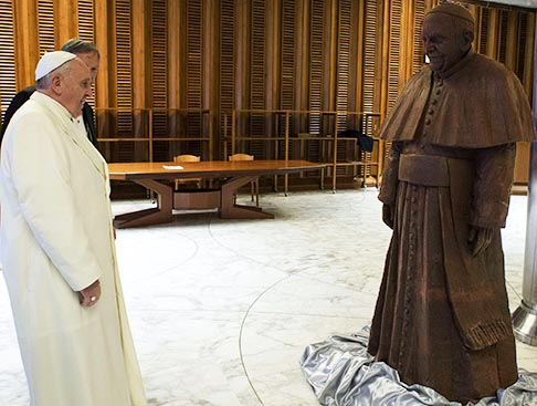 Pope Francis looks at a life-sized replica of himself made entirely out of chocolate in Paul VI Hall at the Vatican Feb. 5. The chocolate image is made of 1.5 tonnes of cocoa.