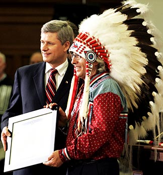 Canada's Prime Minister Stephen Harper presents Assembly of First Nations Chief Phil Fontaine with a statement of apology during a ceremony on Parliament Hill in Ottawa in 2008.