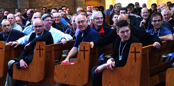 Men attending the Men of Integrity conference at Holy Trinity Church in Stony Plain/Spruce Grove watch some of their peers go through a physical workout at the back of the church.