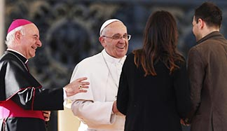 Pope Francis greets Miriam and Marco, an engaged couple who spoke during an audience for engaged couples in St. Peter's Square at the Vatican Feb. 14, Valentine's Day. At left is Archbishop Vincenzo Paglia, president of the Pontifical Council for the Family.