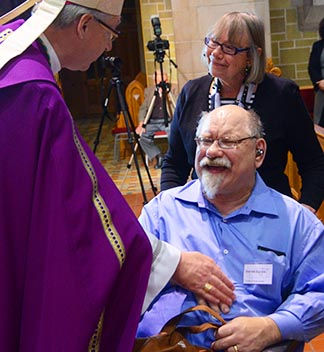 Harold Barnes of Red Deer, accompanied by his sponsor Diane McDonnell, is welcomed into the elect by Archbishop Richard Smith March 9 at St. Joseph's Basilica.