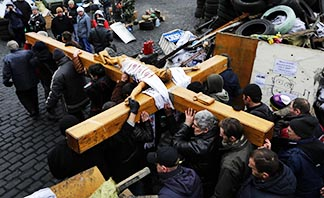 Mourners carry a wooden crucifix in Independence Square in Kyiv, Ukraine, Feb. 25.