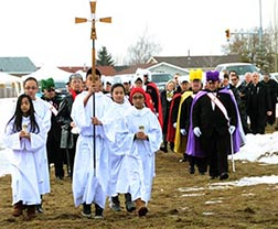 Parishioners and other members of the Catholic community traverse the grounds of the future Corpus Christi Church on March 8.