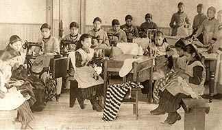 A class of girls learn to sew, knit, weave and keep house at the Qu'Appelle Industrial School in 1892.
