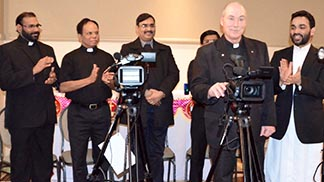Fr. Jim Corrigan plays cameraman at the media launch of Shalom Media Catholic charismatic TV channel while other city priests look on.