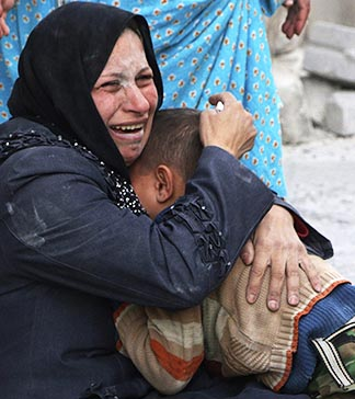 A woman cries as she holds a boy at a site hit by what activists said was a barrel bomb dropped by forces loyal to Syrian President Bashar Assad in Aleppo, Syria, March 6.