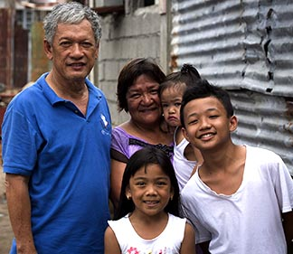 Emmanuel and Maria Rosevilla Margate and the children stand outside their home in Tacloban, Philippines. The family huddled together in their block home Nov. 8, 2013, as Typhoon Haiyan made shambles of many homes in their community.