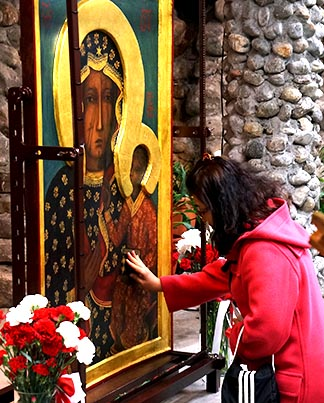 A woman kneels and reaches out and touches a replica of the icon of the Black Madonna.