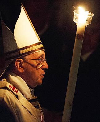 Pope Francis carries a candle as he arrives to celebrate the Easter Vigil in St. Peter's Basilica at the Vatican April 19,