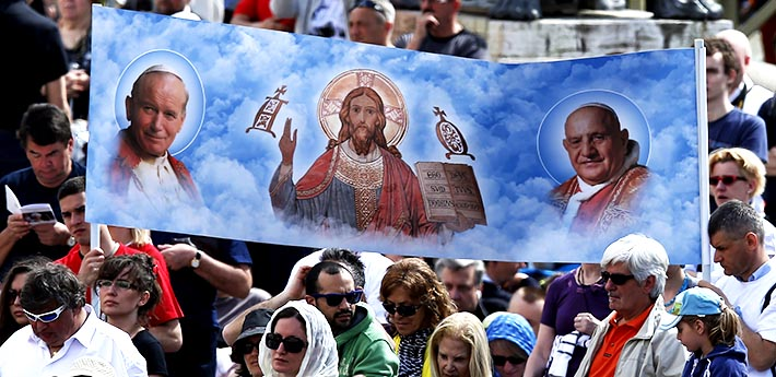 A banner shows new Sts. John Paul II and John XXIII and Jesus during an April 28 Mass of thanksgiving for the canonizations of the new saints in St. Peters Square at the Vatican.