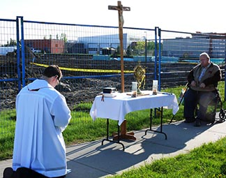 Fr. Matthew Hysell and Yvon Levesque were among those taking part in Eucharistic Adoration May 30 next to the construction site for the future Corpus Christi Church