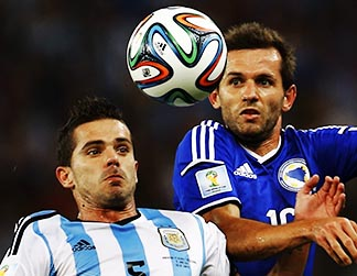 Argentina's Fernando Gago and Bosnia's Senad Lulic battle for the ball during their World Cup soccer match at Maracana stadium in Rio de Janeiro June 15.