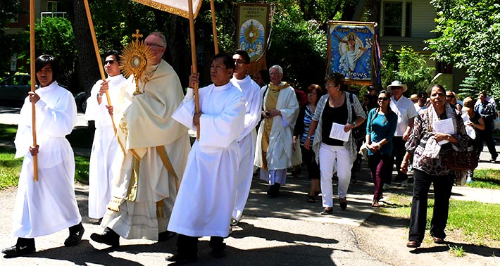 Archbishop Richard Smith carries the Blessed Sacrament down a residential street during the June 22 Corpus Christi procession.