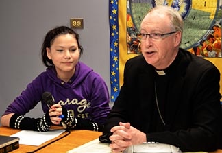 Archbishop Richard Smith, seen here with student Josephine Larocque, told St. Francis school students Pope Francis was pleased with them.