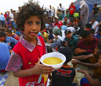 A child holds a bowl of soup inside the Khazer camp on the outskirts of Irbil, Iraq, June 29.