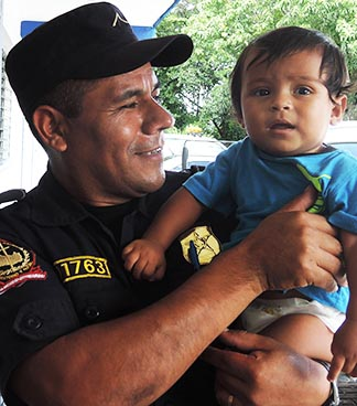 A Salvadorian policeman holds an infant who arrived back in San Salvador from Mexico.