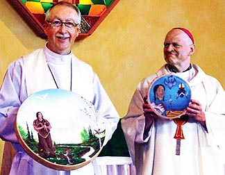 Edmonton Archbishop Richard Smith and Mackenzie Bishop Mark Hagemoen hold up drums they exchanged that depict aspects of their respective dioceses.
