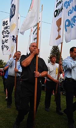 Tall banners are carried first in the lengthy entrance process at the pilgrimage's vigil Mass.