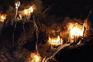 Pilgrims leave candles, symbolic of their prayer intentions, burning on the grotto following the Eucharistic procession after Mass.