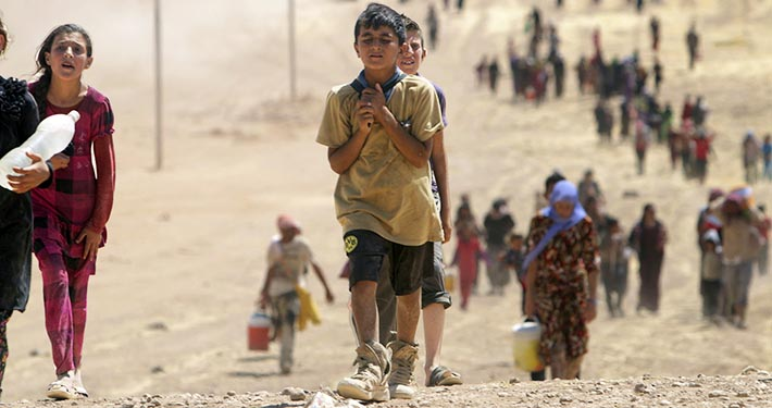 Children flee violence from forces loyal to the Islamic State in Sinjar, Iraq, Aug. 10. Tens of thousands of Iraqis have been forced to flee their country.