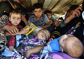 A woman and several children, who fled from violence in Nineveh province in Iraq, arrive in a covered truck at Sulaimaniya province Aug. 8.