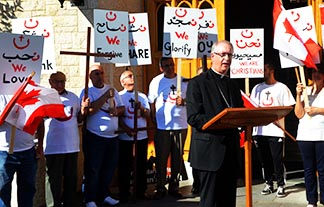 Archbishop Richard Smith, surrounded by members of Our Lady of Good Hope Maronite Parish, addresses local media Aug. 27 on the local Church's response to the suffering and violence in the Middle East.