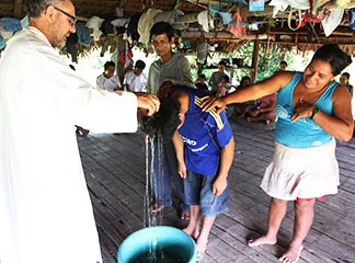 An Augustinian priest baptizes a young man in a village along the Urituyacu River in Peru