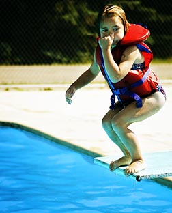 Girl wearing a life jacket jumping off a diving board