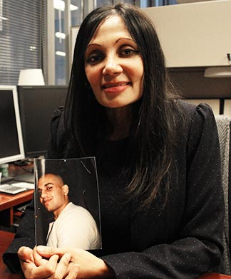 Eileen Mohan holds a photo of her murdered son Christopher in her office.