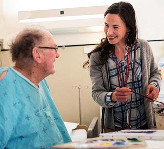 St. Paul Hospital artist-in-residence Marlessa Wesolowski (right) works on a painting with patient Stan Macdonald.