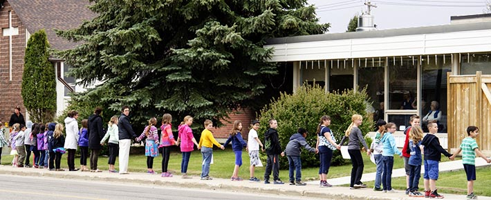 Students at Red Deer's St. Martin de Porres School form a solidarity circle around West Park Lodge and bless its residents.