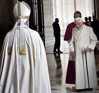 Retired Pope Benedict XVI prepares to greet Pope Francis during the opening of the Holy Door of St. Peter's Basilica at the Vatican on December 8, 2015.