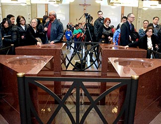 Attendees at Mass file past Corpus Christi's baptismal font as they leave the church