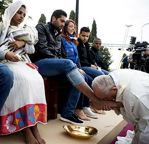 Pope Francis kisses the foot of a refugee during Holy Thursday Mass at a centre near Rome.