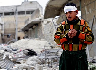 An injured boy stands amid rubble outside his home in 2014 after airstrikes in Aleppo, Syria.